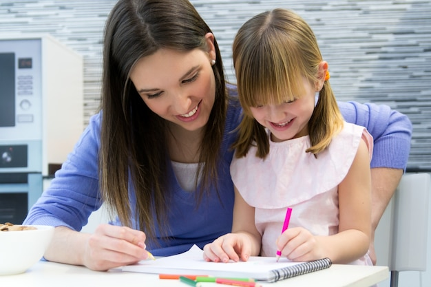 Child drawing with crayons with her mom at home Free Photo