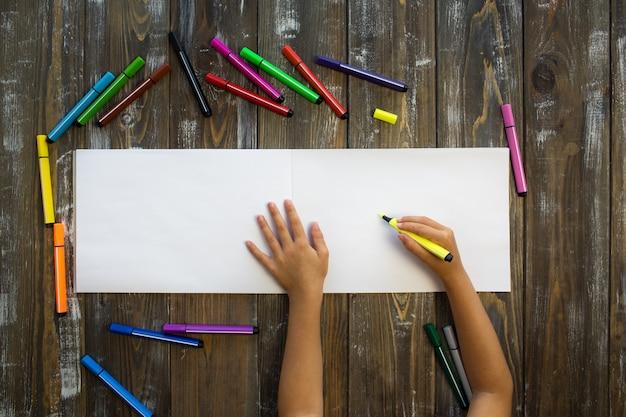 Child draws in a notebook Premium Photo