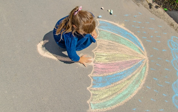 Child draws with chalk on the pavement Premium Photo