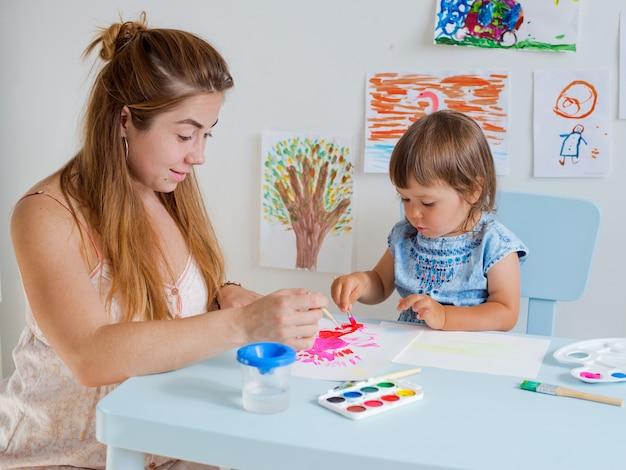 Child draws with teacher Premium Photo
