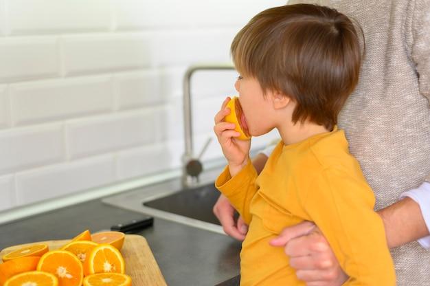 Child eating an orange side view Free Photo