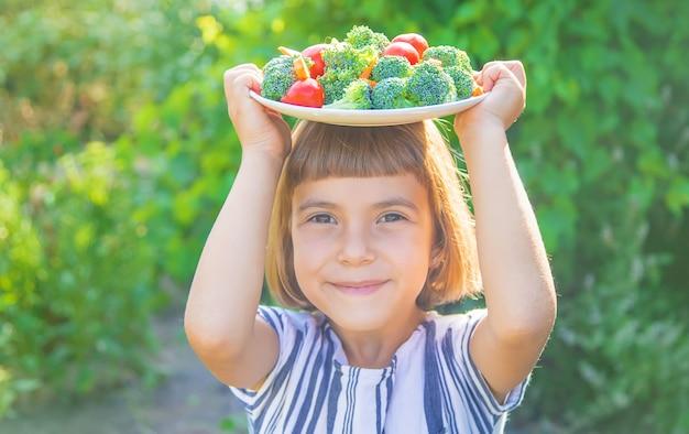 Child eats vegetables broccoli and carrots Premium Photo