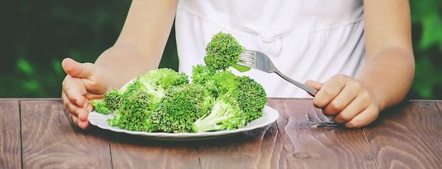 Child eats vegetables. summer photo. selective focus Premium Photo