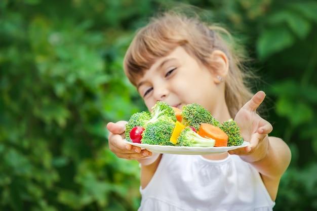 Child eats vegetables. Premium Photo