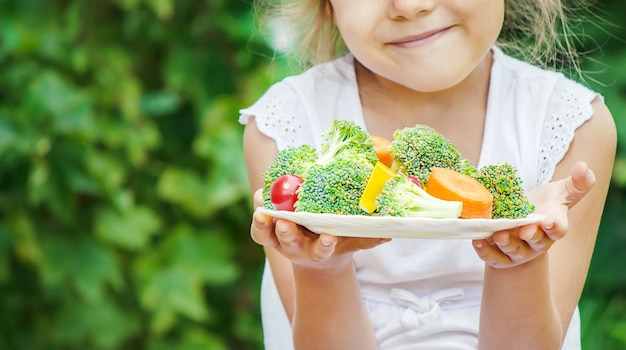 Child eats vegetables. Premium Photo