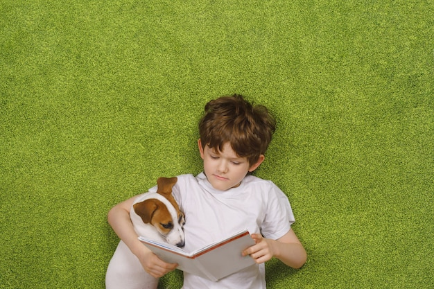Child embracing friendly dog jack russell was reading the book Premium Photo