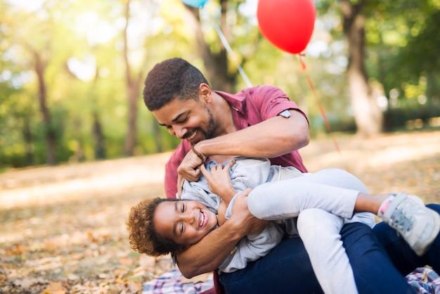 父親が彼女をくすぐっている間、子供は楽しんで笑います 無料写真