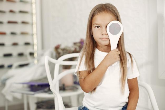 Проверка зрения у ребенка и проверка зрения. маленькая девочка, проверяющая глаза, с фороптером. проверка зрения для детей Бесплатные Фотографии