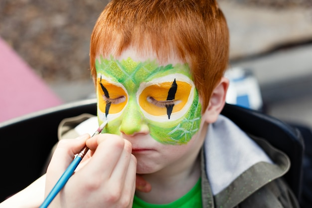 Child face painting process on redhead boy Premium Photo