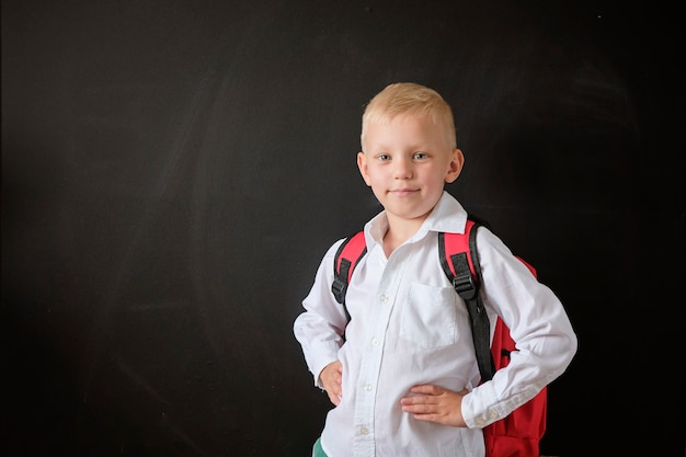 Child from elementary school with bag at blackboard. Premium Photo