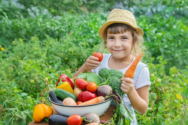Child in the garden with vegetables in his hands. Premium Photo