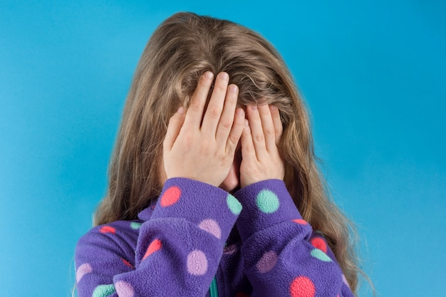 Child girl covered her face with hands Premium Photo