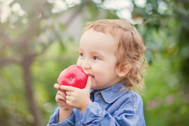 Child girl eating an apple in a garden in nature Premium Photo