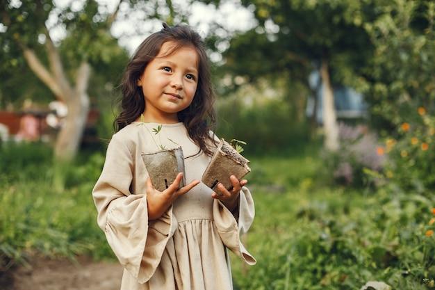 地面に植える準備ができている苗を保持している子供の女の子。茶色のドレスを着た小さな庭師。 無料写真