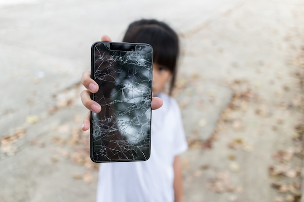 Child girl holding a broken smartphone and broken touch screen on hand Premium Photo