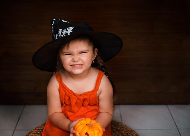 Ребенок девочка держит украшение на хэллоуин джек-о-фонарь на маленьких руках на деревянном фоне Premium Фотографии