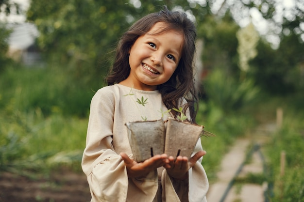 Child girl holding a seedlings ready to be planted in the ground. little gardener in a brown dress. Free Photo