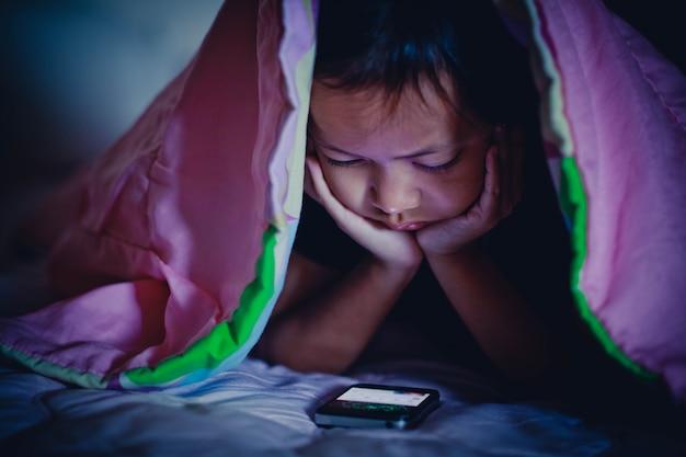 Child girl looking at smartphone in dark under blanket Premium Photo
