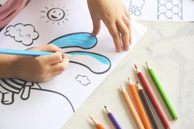 Ребенок девочка рисует на листе бумаги цветными карандашами Premium Фотографии