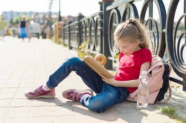 Child girl student wearing glasses reading book Premium Photo