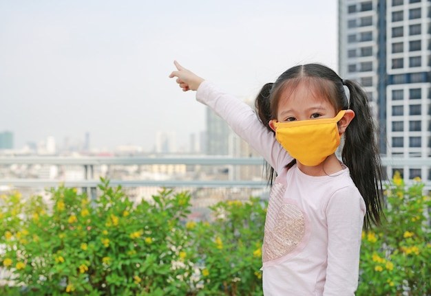 Child girl wearing protection mask with pointing up. Premium Photo