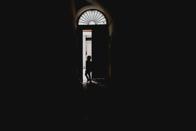 Child going out through a backlit door, concept of loneliness and absence in childhood. Premium Photo