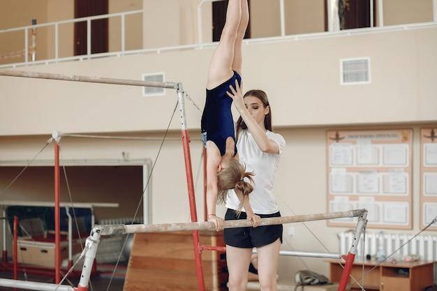 어린이 체조 균형 빔. 체조 대회에서 운동 가로 막대 동안 여자 체조 선수. 자녀와 함께 코치하십시오. 무료 사진