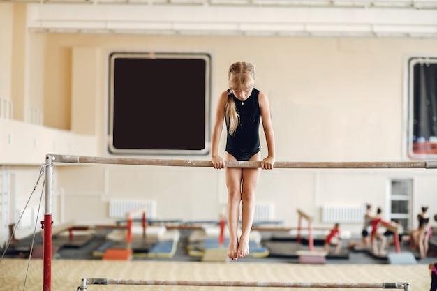 어린이 체조 균형 빔. 체조 대회에서 운동 가로 막대 동안 여자 체조 선수. 무료 사진