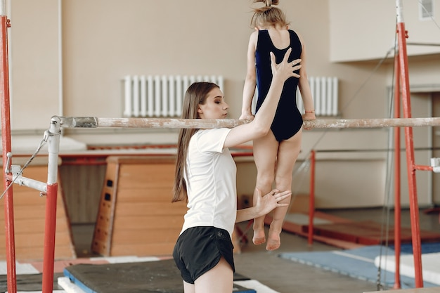 Free Photo   Child gymnastics balance beam. girl gymnast athlete during an exercise horizontal bar in gymnastics competitions. coach with child.