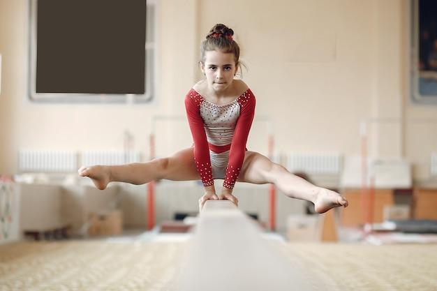 Fascio di equilibrio di ginnastica del bambino. atleta ginnasta ragazza durante una barra orizzontale di esercizio nelle competizioni di ginnastica. Foto Gratuite