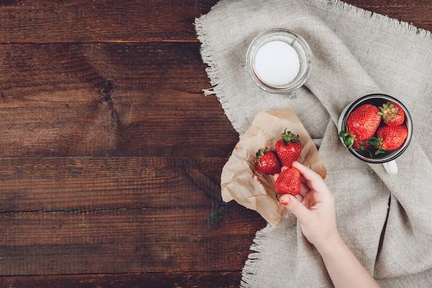 Child hand holding strawberry Premium Photo