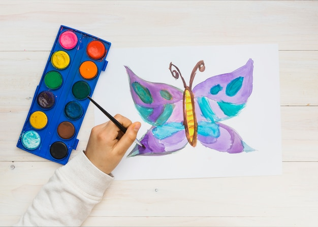 Child hand painting beautiful butterfly drawing on white sheet Free Photo