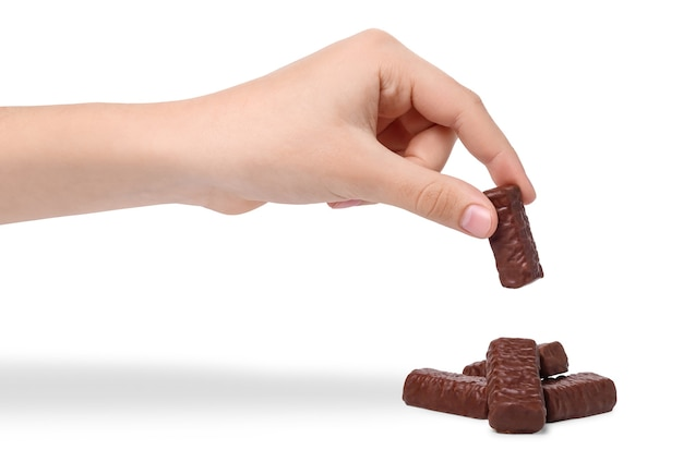 Рука ребенка принимает шоколадные конфеты, изолированные на белом фоне. рука шоколадные конфеты над кучей конфет. Premium Фотографии