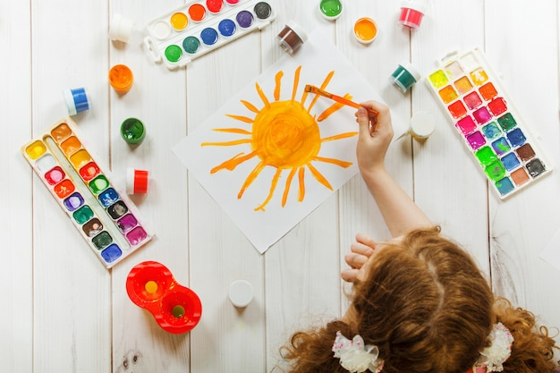 Child hand with brushes drawing on white paper yellow sun. Premium Photo