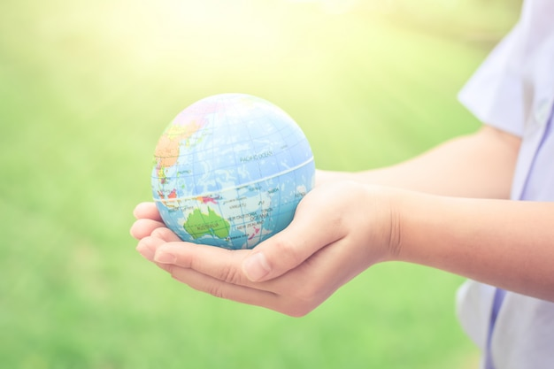 Child hands holding earth concept for caring the planet or save earth concept. Premium Photo