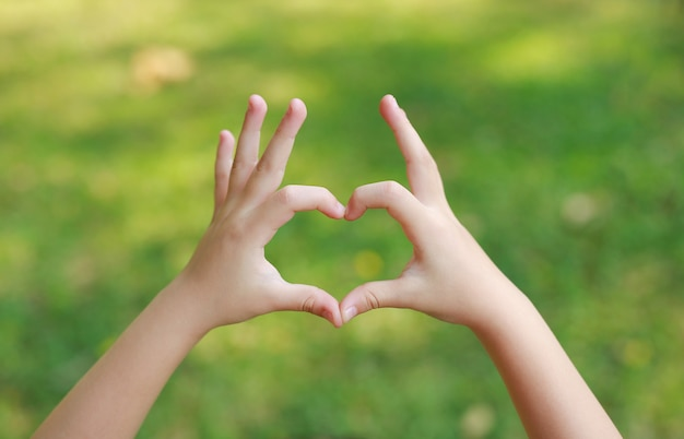 Child hands with heart sign on blur green lawn. Premium Photo