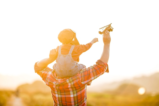 Child and her father with toy airplane in nature at sunset Premium Photo