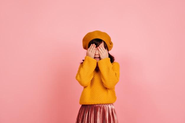 분홍색 벽에 얼굴을 숨기는 아이. 무료 사진