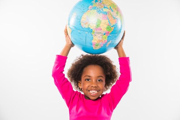 Child holding globe over head in studio Free Photo