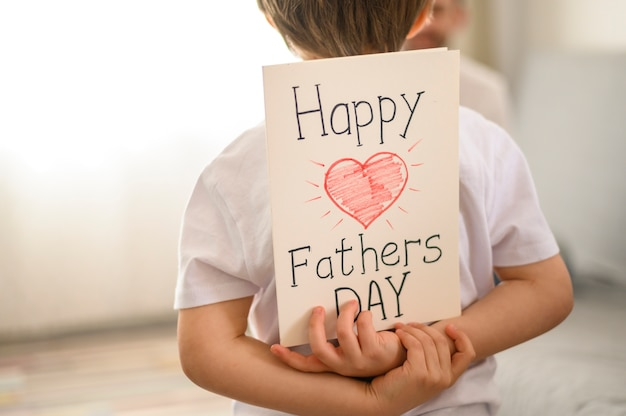 Child holding surprise greeting card Free Photo