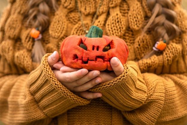 Ребенок держит маленькую тыкву на хэллоуин Premium Фотографии