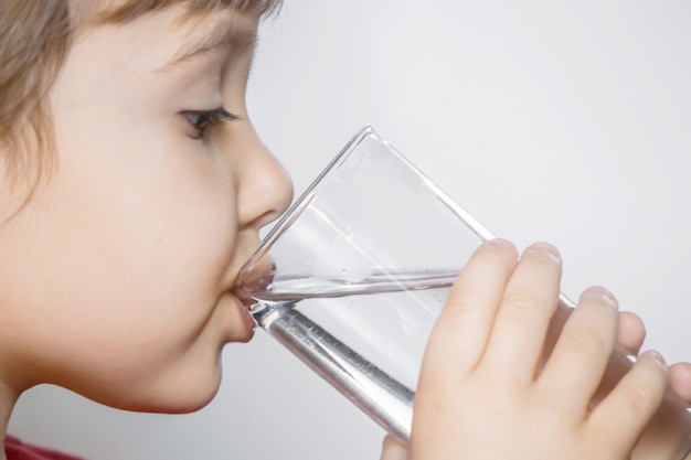 The child holds a glass of water in his hands. selective focus. Premium Photo