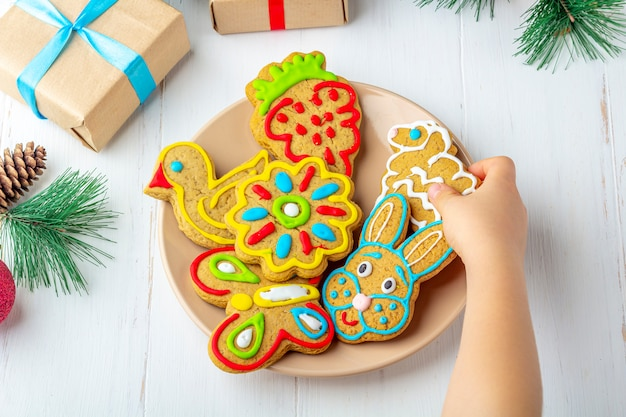 Child holds a homemade painted gingerbread (cookie) on white wooden background among fir branches and gifts. christmas and new year sweet gift concept. funny sweet food close-up. Premium Photo
