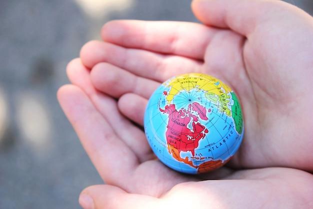 子供は彼の手で地球を保持します Premium写真