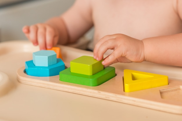 Child at home is manipulating montessori material to learn Premium Photo