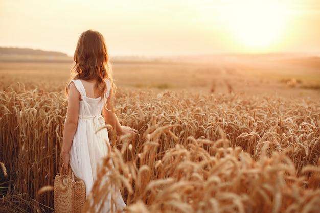 Ребенок в поле летней пшеницы. маленькая девочка в милом белом платье. Бесплатные Фотографии