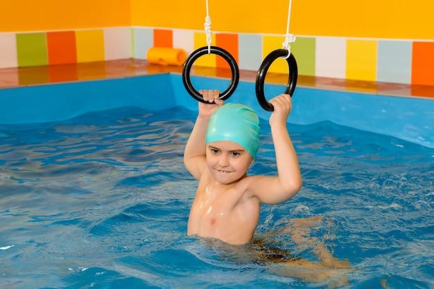 Ребенок в бассейне, тренируясь со спортивными кольцами Premium Фотографии