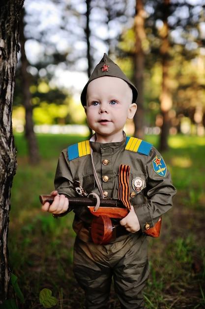 Ребенок в военной форме на фоне природы Premium Фотографии