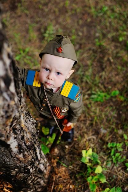 Ребенок в военной форме на природе Premium Фотографии