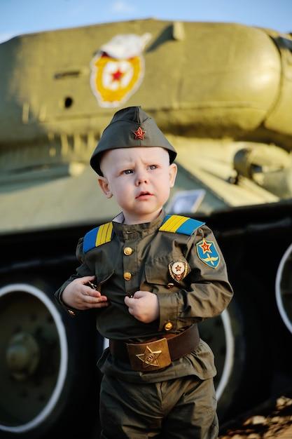 タンクの背景に軍服の子供 Premium写真